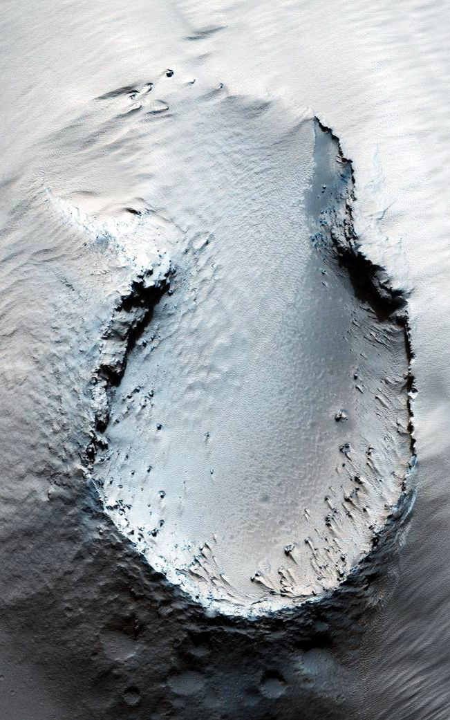 "'Fountain' | Originally released May 30, 2007, this image is centered on a small cone on the side of one of Mars' giant shield volcanoes. The cone shows some layers of hard rock but most of it is made of relatively soft material. This appears to be an example of a ""cinder"" cone composed of pieces of lava thrown into the air during a small volcanic eruption."