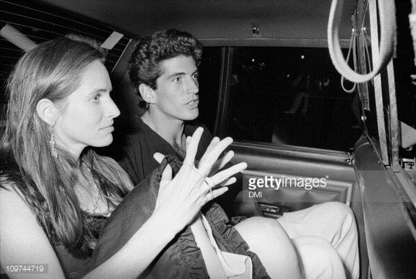 American magazine publisher and Kennedy heir John F. Kennedy Jr. (1960 - 1999) with his girlfriend, actress Christina Haag sit in a taxi as they arrive at Madison Square Garden for Madonna's benefit performance for amFAR, New York, New York, July 11, 1987.