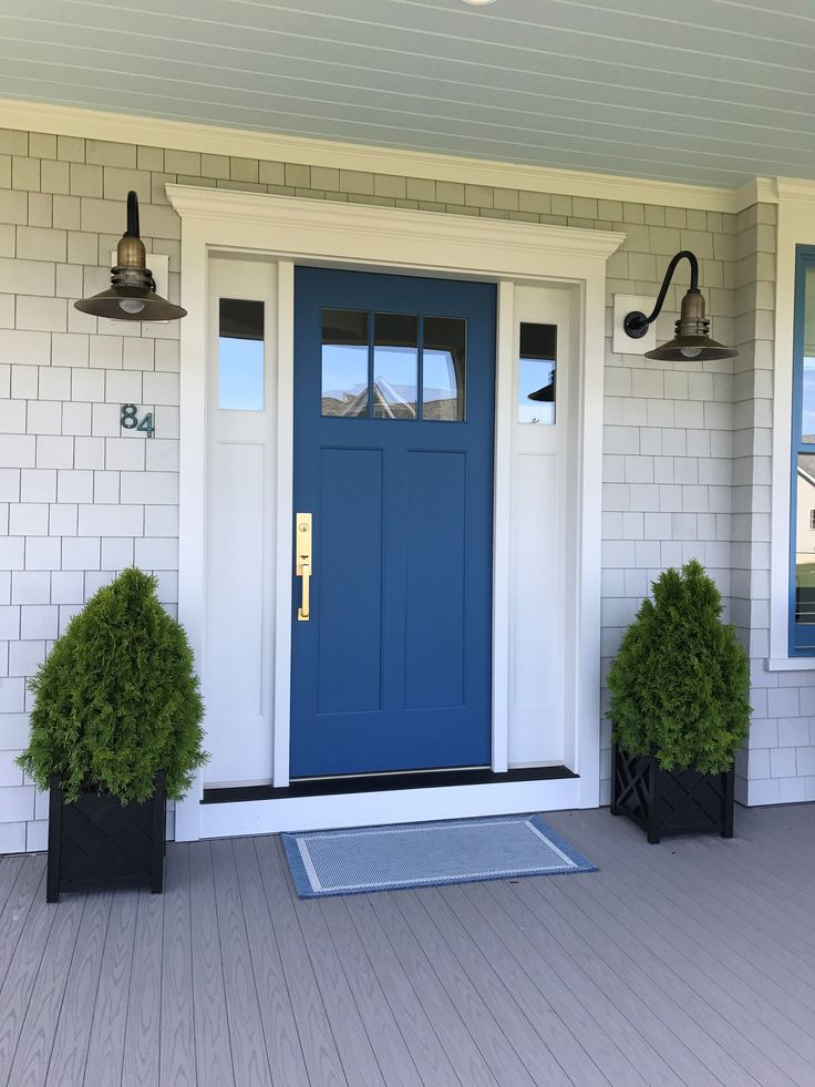 Satin brass hardware by Emtek pops brightly against the front door in Chinese Porcelain by Olympic, and classic industrial gooseneck lights by Barn Light Electric cast a warm, welcoming glow.