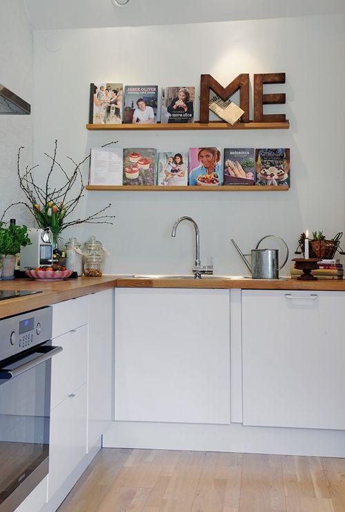 cozinha com prateleira  armarios brancos piso madeira