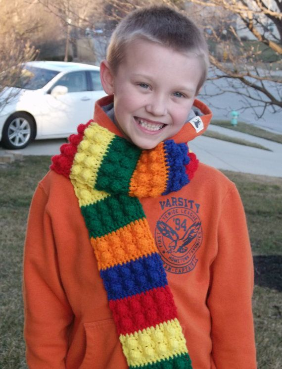 Original scarf inspired by Legos! Perfect for kids of all ages. Crocheted with acrylic yarn in bright primary colors. Scarf measures approximately 4 wide by 55 long. It has 25 bricks and matching fringe. Warm, playful and fun accessory.  This makes a great birthday, Christmas or holiday gift. No worries about duplicating a gift with this unique scarf.   Created in my smoke free, pet free home studio.