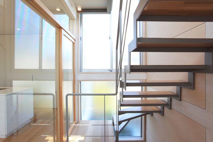 ダイニングキッチンとガラスで仕切られた階段室は光が溢れ、部屋に採光をもたらす。