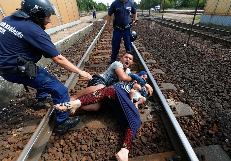 I poliziotti cercano di allontanare una famiglia di migranti dai binari ferroviari a Bicske in Ungheria, il 3 settembre 2015. - Laszlo Balogh, Reuters/Contrasto