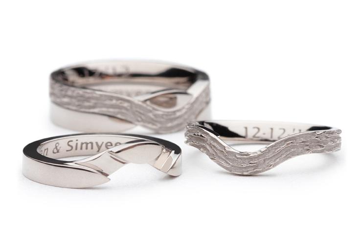 Twee identieke witgouden puzzel trouwringen. De trouwringen bestaan ieder uit twee ringen die in elkaar grijpen en zo één trouwring vormen. De ene ring is glad en hoogglans uitgevoerd. De andere ring heeft een mat, ruw doorlopend reliëf.