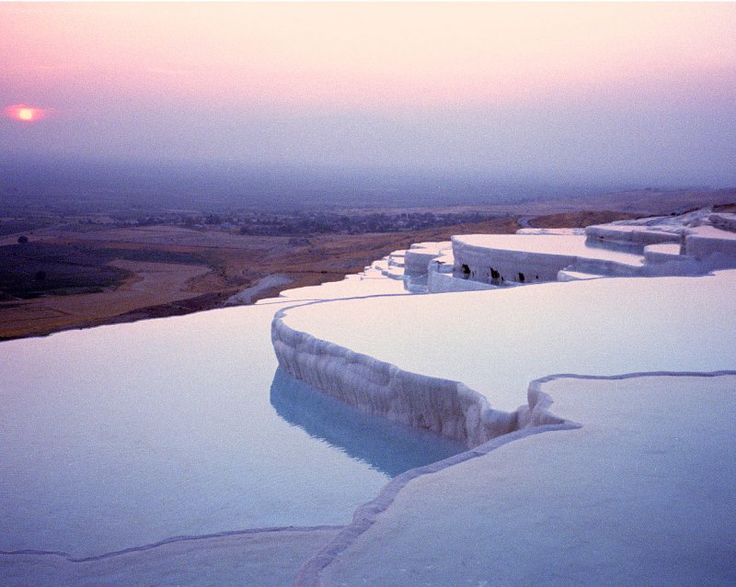 Pamukkale, Turkey | The water (35 degrees Celsius, 95 degrees Fahrenheit) which is flowing down the cliff of Pamukkale has turned the area into as white as cotton color, and carved this fantastic formation of stalactites and basins.