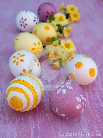 Easter eggs and primrose flowers on the violet board