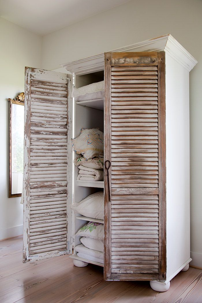 To give an old bookcase a touch of cottage style, attach two shutters to use as doors. Don't worry about painting them; a little patina adds to the charm.