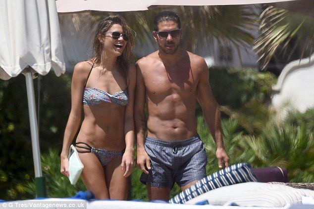 Atletico Madrid manager Diego Simeone walks alongside his girlfriend Carla Pereira in Marb...