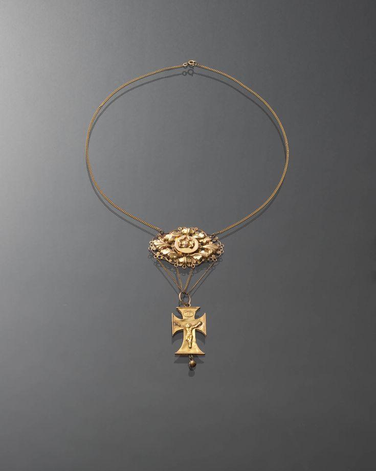 Gouden ketting met een hanger en een kruishanger. Gedragen door een rooms-katholieke vrouw uit Blaricum. De vervaardiger is onbekend (geen meesterteken). De ketting en de hanger zijn ongewaarborgd. In het kruisje staat een gehaltemerk dat gebruikt is tussen 1853 en 1906.  #Blaricum #Gooi #NoordHolland