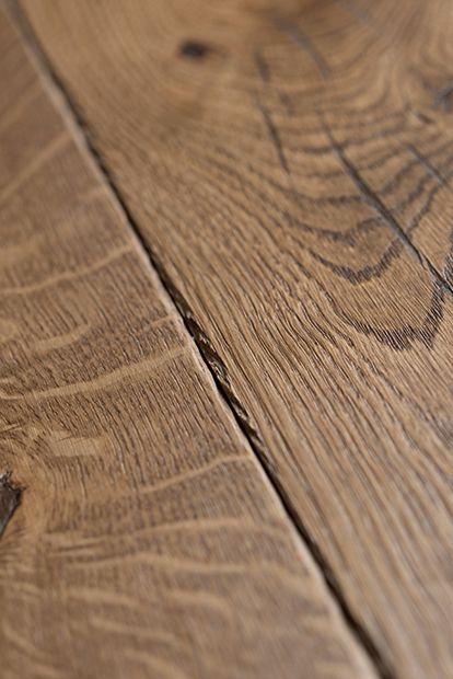 Focus matière sur le parquet en chêne avec des chanfreins vieillis. Référence : Origine Cuir Otello, collections PANAGET.