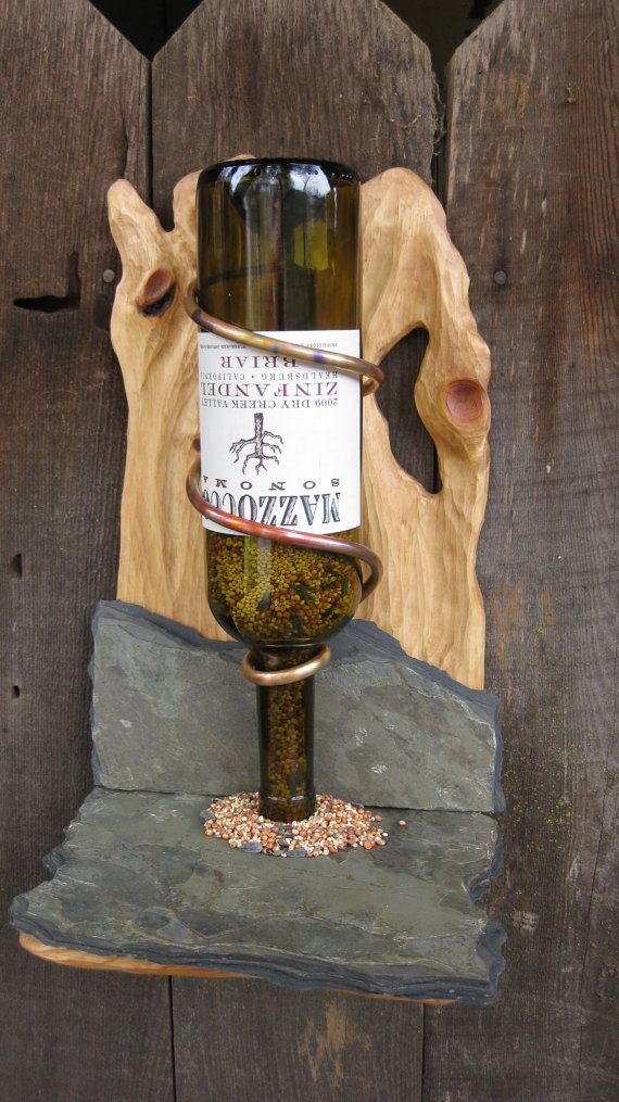 This is a beautiful, unique, and rustic one of a kind, hand-crafted bird feeder. It is sculpted pine with a rustic and durable slate base. Built to last for years, it makes a beautiful addition to any yard or garden. The wine bottle shown is included; the bottle can be replaced with any 750 ml wine bottle by simply adjusting the copper coil to fine tune the height. Bird seed not included. This bird feeder is designed to hang on a wall, post, fence, or tree with included hardware.