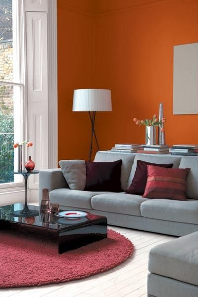 Large windows in this living room ensure plenty of light, allowing for deeply colored walls in Glidden's Fresh Tangerines, and accents. | Photo: Courtesy of Glidden | thisoldhouse.com