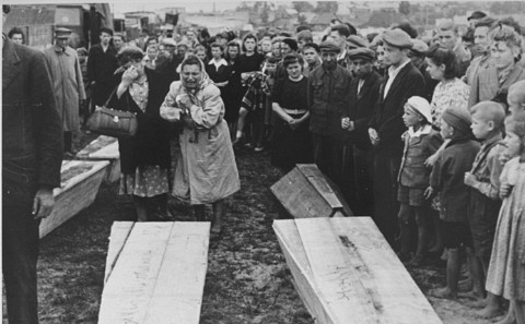Two women grieve over the coffins of those killed in the Kielce pogrom as they are transported to the burial site in the Jewish cemetery.