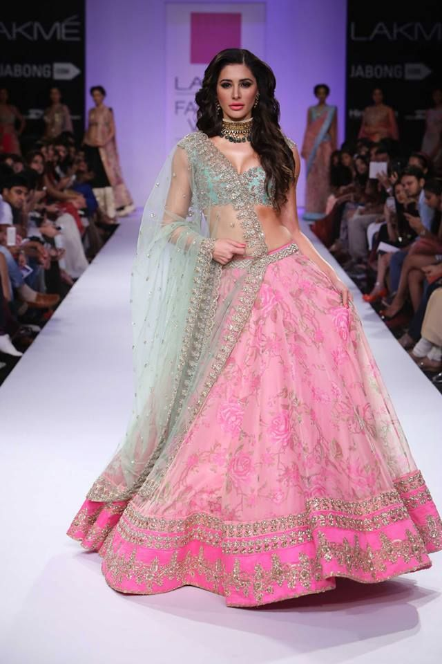 Actress Nargis Fakhri walked the ramp in a soft pastel pink print net lehenga, green choli and tulle dupatta by Anushree Reddy, complemented by a gold and emerald choker.