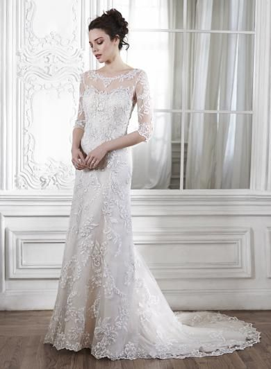 Maggie Sottero VERINA - Dramatický priehľadný chrbát s čipkou a čipkované rukávy zdobia tieto luxusné puzdrové svadobné šaty. Sú pôvabné, ľahučké, splývavé a ženské, umocnené metalickými čipkovými aplikáciami vyšívanými Swarovski krištálikmi od ramien až po zem.