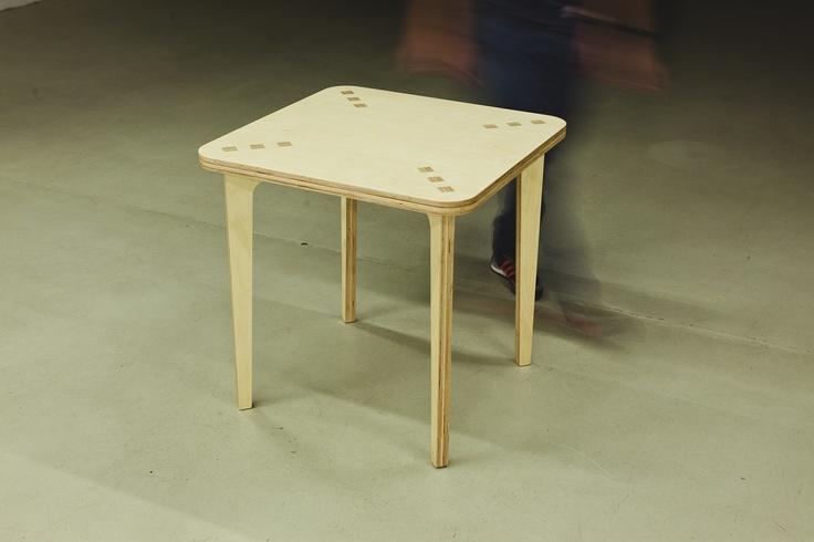 Combina Cookie Table - Masa de bistro pentru patru persoane. Foloseste o singura foaie de placaj multistratificat. Este asamblata fara niciun element metalic. Picioarele (dispuse la 45 de grade, pentru o buna stabilitate) se imbina cu blatul si formeaza la suprafata acestuia o retea de 12 patrate cu aspect de intarsie.  Partea inferioara a blatului este decupata pentru a reduce masa si pentru a crea o zona perimetrala utila la deplasarea mesei.  Placaj multistratificat de mesteacan.