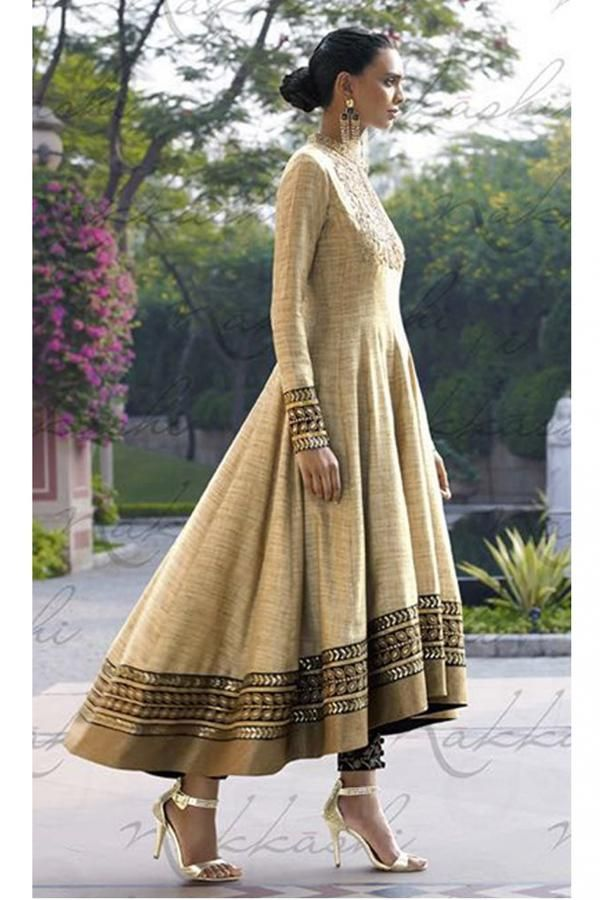 This glittering textured khadi fabric anarkali dress is in beige color. The yoke portion of the suit has heavy embroidered glittering flowers and florals design with embellishments of stone and sequins work. The border of the sleeves has intricate embroidered black laces decorated with heavy embellishments of stone and leafy florals followed by beige lace border. The black churidaar has embroidered traditional design. -www.cooliyo.com