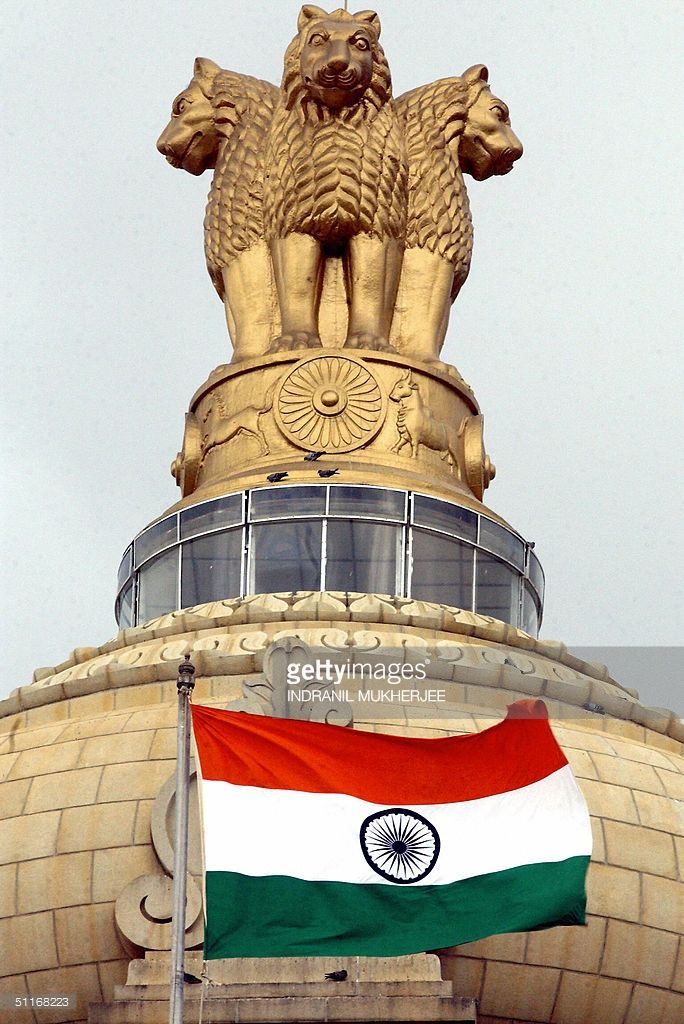 The Indian national flag flies in front of the Indian national emblem, lying atop the Vidhana Soudha State assembly in Bangalore, 14 August 2004 on the eve of India's 57th anniversary of Independence. The emblem, made of four lions, standing back to back, was adopted 26 January 1950 as India's national emblem following the end of British rule. India has stepped up security across the country ahead of Sunday's Independence day celebrations, especially in flashpoint areas of Indian Kashmir as…