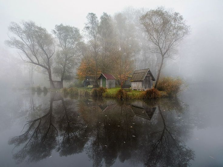 Picture of a small cabin reflected in a lake on a misty day in Szodliget, Hungary