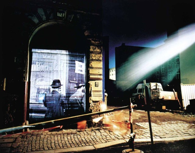 """Shimon Attie: For his 1991–93 project, """"The Writing on the Wall,"""" Attie projected images of pre-World War II life in the Scheunenviertel, the former Jewish quarter in Berlin, at the same locations of the original images. The juxtaposition of images of working-class Jewish life on the facades of buildings in the then newly gentrifying neighborhood highlight the changes in the changes in the city and its inhabitants."""