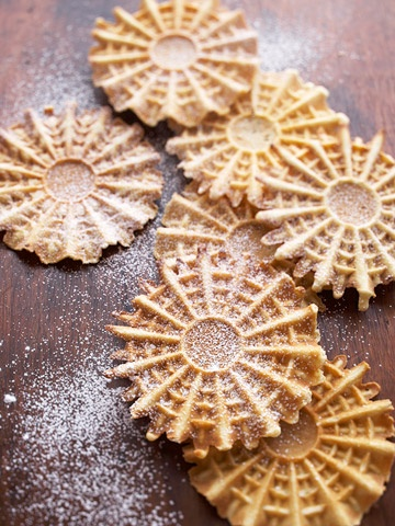 """Pizzelle's come from Italy. They are also known as Italian wafer cookies and there are various ways which to spell pizzelle such as """"piazelle,"""" """"piazella,"""" """"pizzele"""" and """"pizelle."""" The name comes from the Italian word """"pizze"""" for round and flat."""