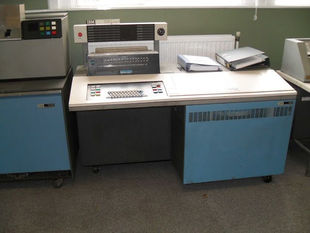 IBM 1130 Data Processing System [A popular system starting in 1965. Data typed into the keypunch(Right) was encoded onto cards which were fed into the card reader(Left). There was a small disk drive behind the vented blue panel door, on the lower right. The large bright red switch(Upper Left) was seldom visible except in marketing photographs. It was a panic button that killed power until a very expensive IBM tech came around to fix it. The switch was often hidden with a smiley face…