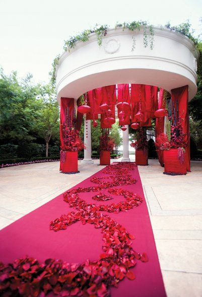 Ceremony site featuring a red runner with rose petals leading to an altar of hung lanterns, tapestries and mixed blossoms. --Wedding Style Magazine