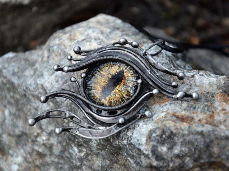 """Přívěsek """"Dragon eye""""  Autorský přívěsek vytvořený kombinací technik wire wrapping a cínování z bezolovnatého cínu.  Přívěsek doplňuje ručně malovaný kabošon s motivem oka o průměru 25 mm a je zavěšen na černé kulaté kůži o délce 50 cm se zapínáním na karabinku.  Šířka přívěsku 5 cm, výška 7 cm, váha 21 g. Patinován, leštěn a ošetřen antioxidantem."""