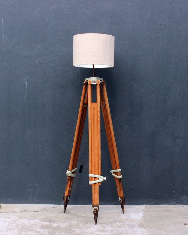 A surveyor would have used this wood and metal tripod to hold surveying instruments in order to measure land. We've turned it into an adjustable standing light.