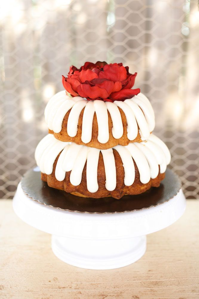 Simple iced bundt cake with a red floral topper.  Photo by Aaron Snow Photography. www.wedsociety.com  #wedding #cake