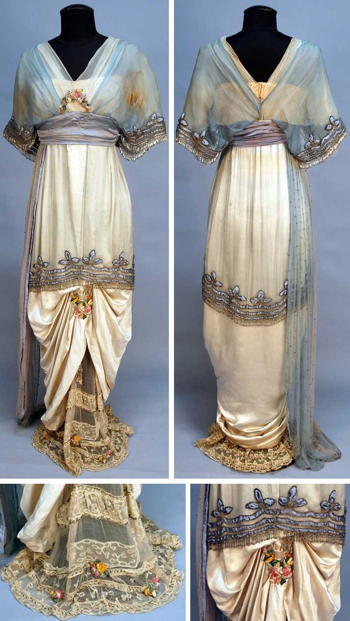 Evening gown, Lucile, ca. 1914. Cream satin. Short-sleeved cream and blue chiffon bodice with V-neck and V-back, trimmed with bands of blue satin, silver metallic cord and crystal beaded fringe and silk flowers. Blue satin cummerbund, hobble skirt beneath short beaded chiffon overskirt, ruched in front to reveal beaded lace and chiffon underskirt and having silk flower swag. Chiffon side drape studded with rhinestones. Whitaker Auctions