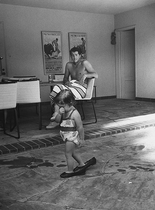 Dean Martin watching his daughter Gina Caroline Martin walking in her mother's shoes at home in Beverly Hills, 1958