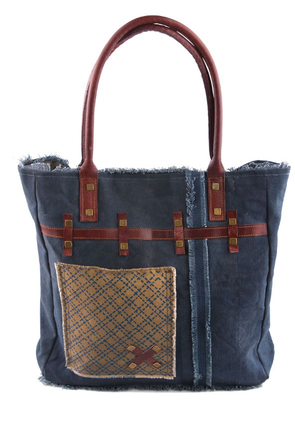 The Indigo Tote Bag by Mona B has a snazzy blue and beige colored patch on dark navy canvas.This beautiful tote features leather handles along with a splash of
