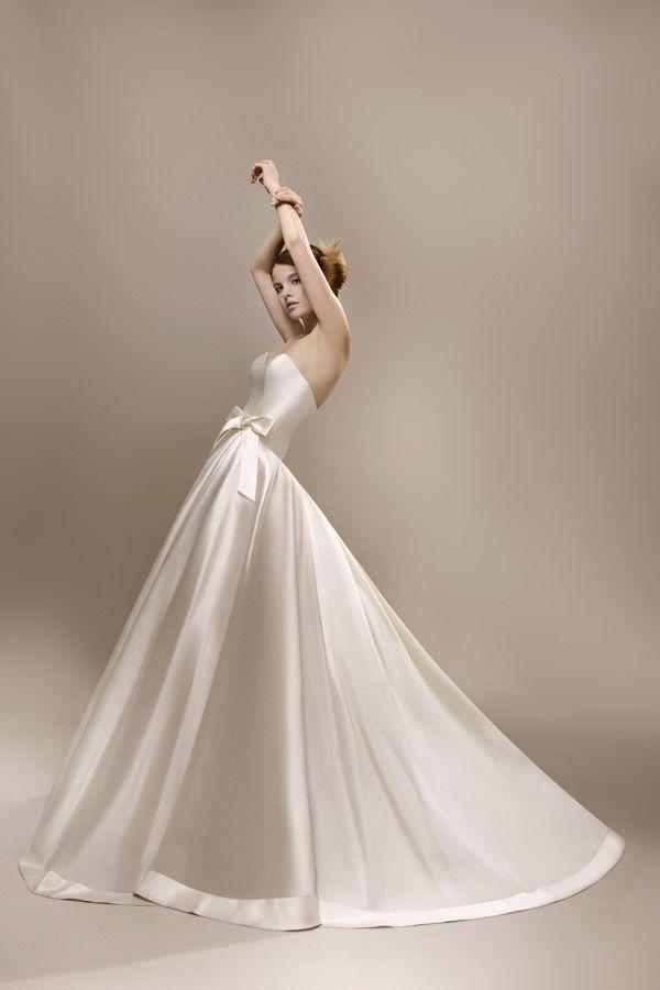 """Robe de mariée en mikado de soie. Jupe volumineuse incrustée de dentelle perlée. Ceinture à la taille formant un nœud sur la jupe. C'est la robe que vous pouvez voir dans le film """"Qu'est-ce qu'on a fait au Bon Dieu?"""""""