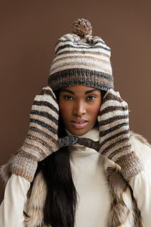 Mod stripes get a boho-chic makeover in two neutral colorways of Silk Garden Sock—deep taupe and black #267 and bright cream, tan and gray #269. The lightweight yarn lends extra slouch to the hat while creating a close fit for the matching mittens. Each piece is worked seamlessly from a snug single-rib border, with wide stockinette stripes forming the body. The hat is shaped at the top, forming a flat crown, and trimmed with a pompom.