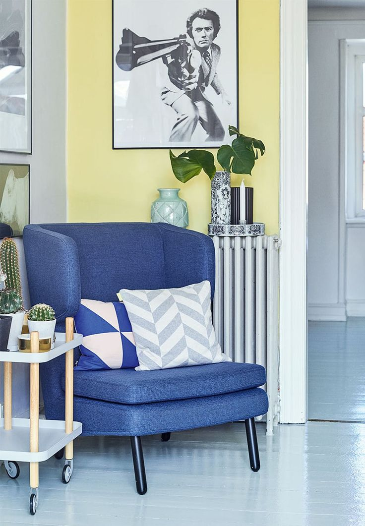 Blue armchair and yellow wall gives a playful and creative feeling in this cozy corner.