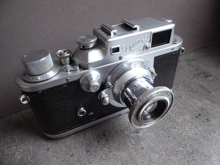 Leica - kopie Zorki 3 Krasnogorsk mechanische plant KMZ USSR  Je biedt op een camera uit een collectie van USSR camera 'sZorki 3 meetzoeker camera (mechanische Krasnogorsk plant KMZ- Sovjet-Unie)Productie periode: 1951-1956Lens: Jupiter - 22 3.5 / 50mm verwisselbare lensSluitertijd: Focal-plaat sluiter - / 1000; een lange tijd aan de voorzijde van de cameraFlash contactSerienummer behuizing: 5429458De camera is visueel in goede conditie en toont alleen lichte sporen van slijtage (zie foto's)…