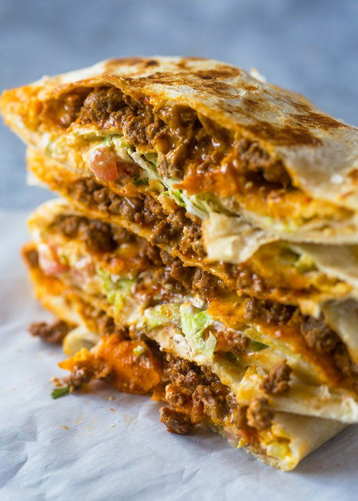 A Large tortilla filled with queso, taco beef, a tostada shell, sour-cream, fresh lettuce, tomato, cilantro, and cheese. This cheesy taco/burrito hybrid packs a ton of flavors & crunch!Ever sin…