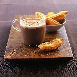 A cup of hot chocolate on a wooden board with a bowl of churros