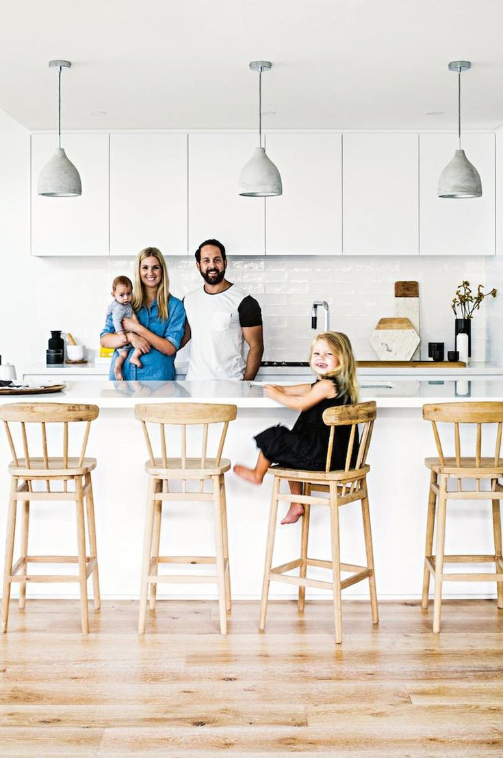 Three grey concrete pendant lights over kitchen island, white handleless cabinets, handmade subway tiles splashback, wooden Ercol-style barstools, timber floorboards, white stone benchtops