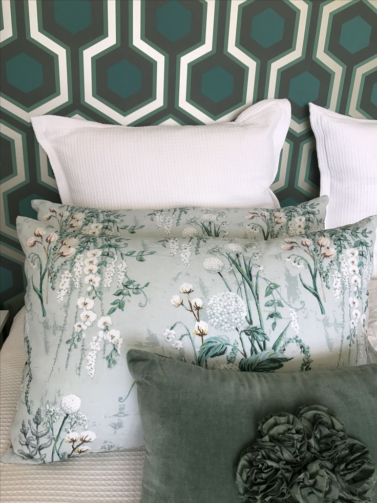 Master Bedroom: Geometric wallpaper team with soft floral and velvet bedding