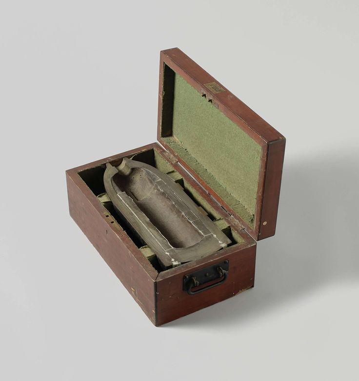 William Armstrong & Co. | 18 cm Segmentgranaat in houten kist, William Armstrong & Co., 1868 | Een halve overlangs doormidden gezaagde puntvormige 18 cm granaat, in een houten kist. De granaat is 45 cm lang en heeft een kaliber van 176 mm. Hij heeft twee ringen bronzen nokken voor een getrokken loop met drie trekkende velden. De neus heeft de vorm van een flessehals met een buisgat. De granaat is hol: de springlading is omgeven door twaalf ijzeren segmentringen, die met lood aaneengekit…