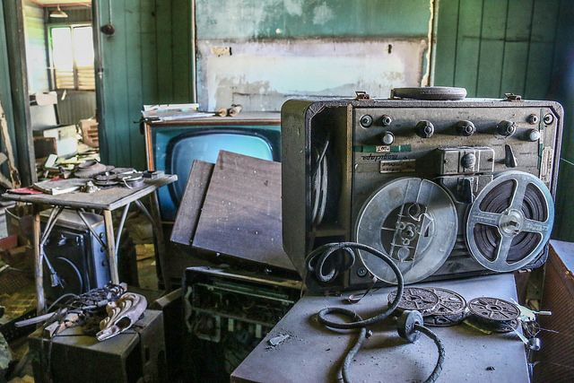 This lonesome tape recorder, and tape rolls sat on top of an old television, hidden in the corner of the cluttered lounge room.