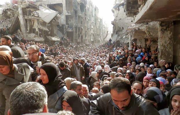 Το δραματικό πρόσωπο του εμφυλίου πολέμου στη Συρία. Παλαιστίνιοι, συνωστίζονται ανάμεσα στα ερείπια για ένα πιάτο φαγητό.