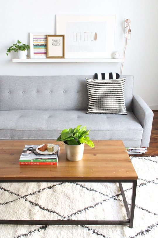 Grey couch, geometric rug, wood coffee table, black and white pillows.