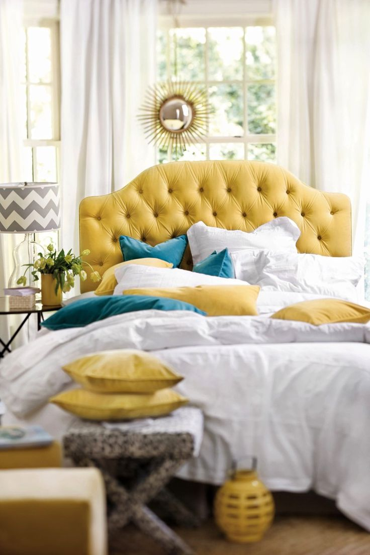 Yellow tufted headboard with blue velvet pillows and white linens