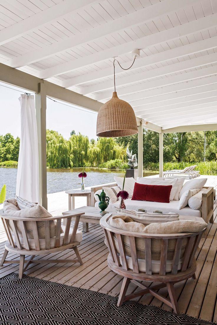 Sillones blancos en gran deck que vincula la residencia con la laguna en una casa de fin de semana en Pilar.