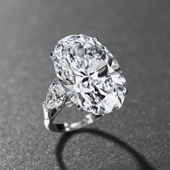 AN IMPORTANT DIAMOND RING, BY GRAFF Set with an oval-shaped diamond, weighing approximately 26.24 carats, to the pear-shaped diamond shoulders, weighing approximately 1.06 and 1.04 carats, mounted in platinum.