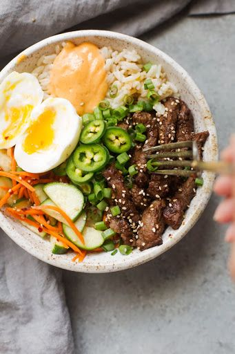 Korean Bbq Bowls With Garlic Scented Rice With Sirloin Steak, Asian Pear, Garlic, Ginger, Onions, Soy Sauce, Sesame Oil, Scallions, Oil, Oil, Garlic, Parboiled Rice, Chicken Broth, Sesame Seeds, Red Pepper Flakes, Rice Vinegar, Honey, Sliced Cucumber, Boiled Eggs