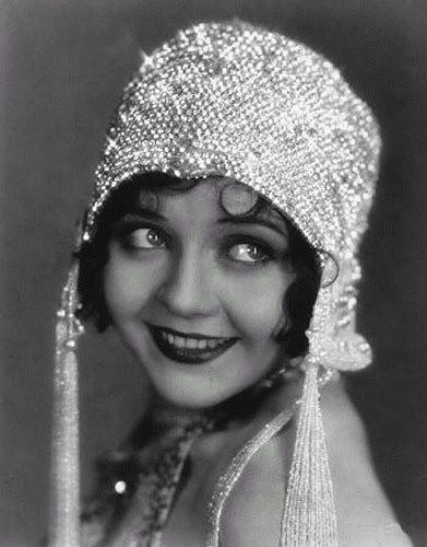 FLAPPER es un anglicismo que se utilizaba en los años 1920 para referirse a un nuevo estilo de vida de mujeres jóvenes que usaban faldas cortas, no llevaban corsé, lucían un corte de cabello especial (denominado bob cut), escuchaban música no convencional para esa época (jazz), que también bailaban. Las flappers usaban mucho maquillaje, bebían licores fuertes, fumaban, conducían, con frecuencia a mucha velocidad.